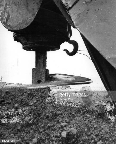 Construction worker Emary Adkins is almost obscured by dirt hurled out by drill which bores holes for the concrete caissons which will support the...