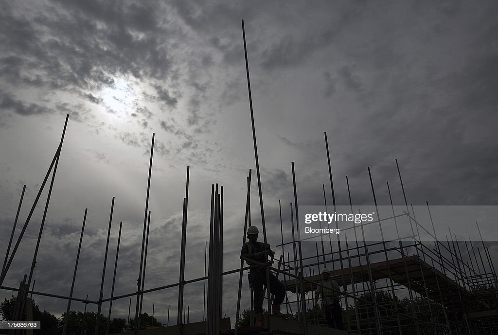 A construction worker erects scaffolding at the Oval Quarter, a shared ownership, private and social residential housing complex developed by Higgins Group Plc in partnership with Nottinghill Housing and Pinnacle Regeneration Group, in London, U.K., on Monday, Aug. 5, 2013. U.K. house prices rose 0.8 percent in July, from 0.3 percent the previous month, Nationwide Building Society said. Photographer: Simon Dawson/Bloomberg via Getty Images