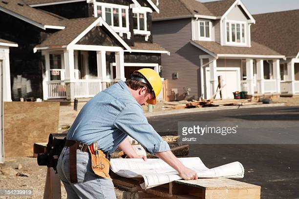 Construction worker examined building plans blueprints