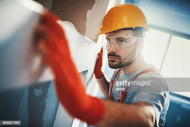 Construction worker examining a drywall.