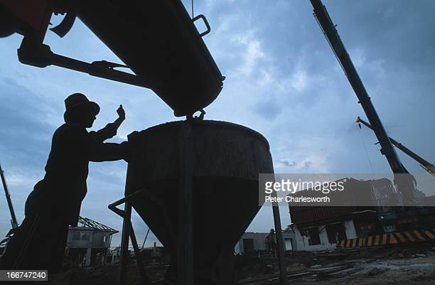 A construction worker fills a hop with Siam City Cement concrete from a cement mixer truck on a huge real estate development housing project in the...