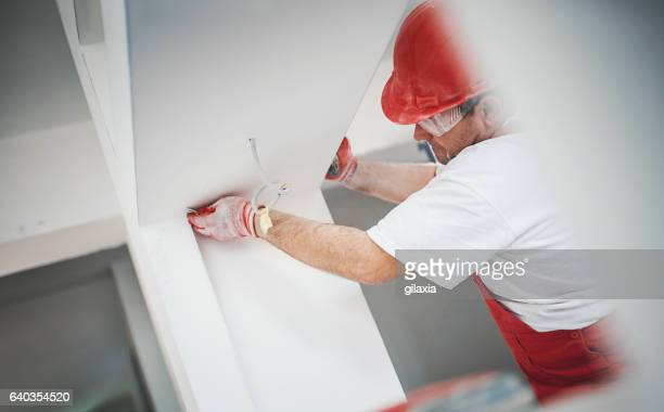 Construction worker finishing a drywall.