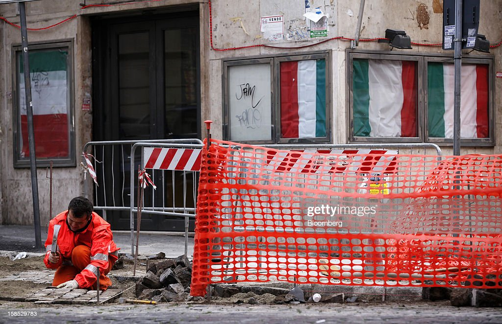A construction worker fixes cobblestones on a road near public noticeboards displaying Italian national flags in Rome, Italy, on Tuesday, Dec. 18, 2012. Italian Prime Minister Mario Monti, who is under pressure from euro-area and business leaders to enter the Italian election campaign, plans to quit once parliament passes his budget this week. Photographer: Alessia Pierdomenico/Bloomberg via Getty Images