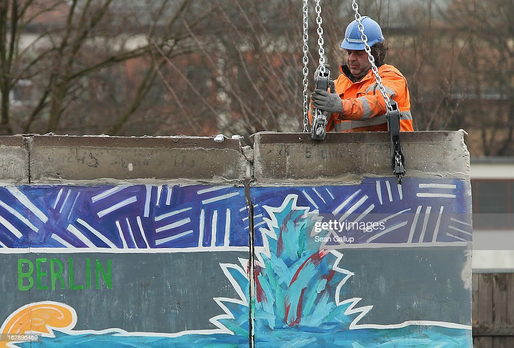 A construction worker fixes equipment to a section of the East Side Gallery, which is the longest still-standing portion of the former Berlin Wall, in roder to remove it with a crane on March 01, 2013 in Berlin, Germany. A real estate developer is planning to build a 14-storey apartment building between the Wall and the Spree River and needs to remove a 25-meter long Wall section in order to allow access to the construction site. Critics, including East Side Gallery mural artists and Spree River embankment development opponents, decry the move, citing the importance of the East Side Gallery's status as a protected landmark and a major tourist attraction. The East Side Gallery is approximately 1.3 kilometers long.