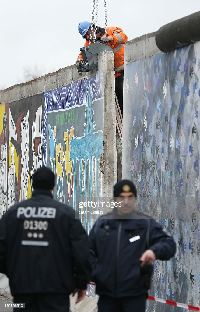A construction worker fixes equipment to a section of the East Side Gallery, which is the longest still-standing portion of the former Berlin Wall, in order to remove it with a crane as police stand nearby on March 01, 2013 in Berlin, Germany. A real estate developer is planning to build a 14-storey apartment building between the Wall and the Spree River and needs to remove a 25-meter long Wall section in order to allow access to the construction site. Critics, including East Side Gallery mural artists and Spree River embankment development opponents, decry the move, citing the importance of the East Side Gallery's status as a protected landmark and a major tourist attraction. The East Side Gallery is approximately 1.3 kilometers long.