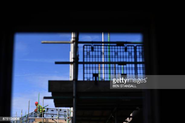 A construction worker gazes from Nansledan housing development championed by Britain's Prince Charles Prince of Wales at Newquay town in Cornwall on...