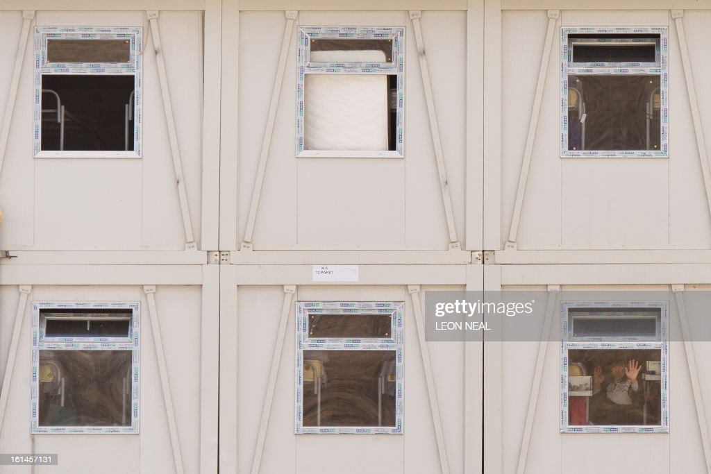 A construction worker gestures from the window of his shared accommodation block in Krasnaya Polyana, near Sochi on February 11, 2013. With a year to go until the Sochi 2014 Winter Games, tests events and World Championship competitions are underway.