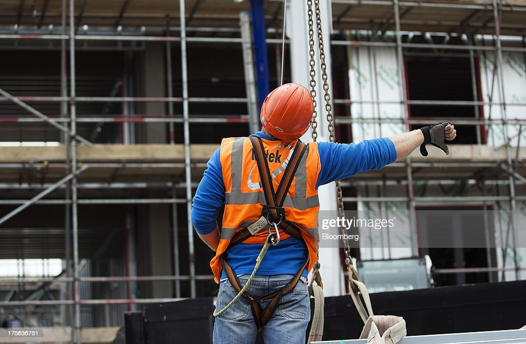 A construction worker gestures while wearing a safety harness at the Oval Quarter, a shared ownership, private and social residential housing complex developed by Higgins Group Plc in partnership with Nottinghill Housing and Pinnacle Regeneration Group, in London, U.K., on Monday, Aug. 5, 2013. U.K. house prices rose 0.8 percent in July, from 0.3 percent the previous month, Nationwide Building Society said. Photographer: Simon Dawson/Bloomberg via Getty Images