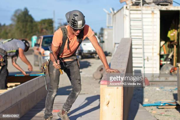 Construction worker hammering in a bolt