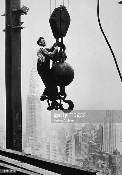 A construction worker hanging on a wrecking ball pulley while working on the Empire State Building in New York The Chrysler building is behind him