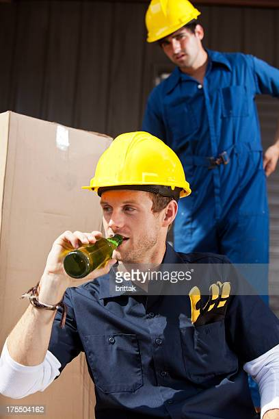 Construction worker having a beer while the foreman watches chritically