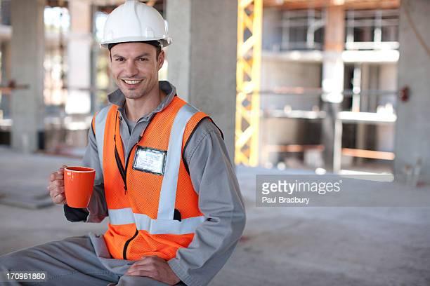 Construction worker having coffee break on construction site