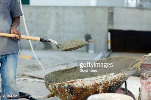 Construction worker holding a shovel with sand : Stock Photo