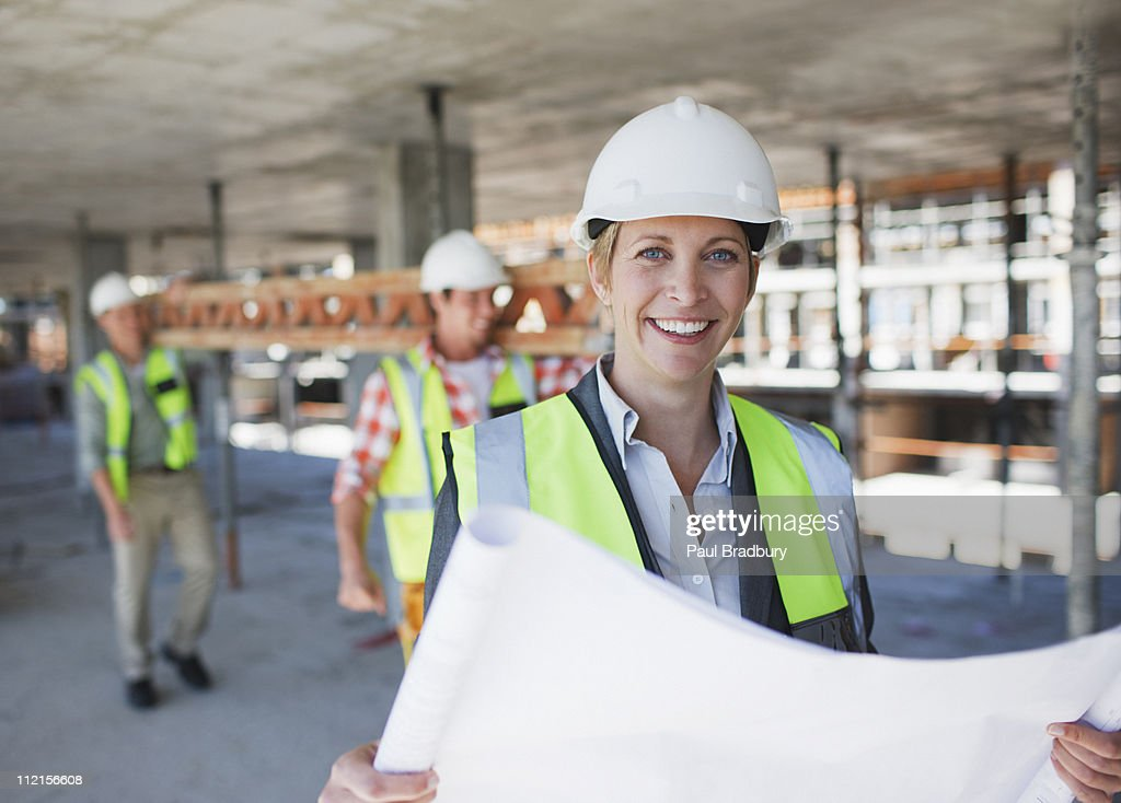 Construction worker holding blueprints on construction site : Stock Photo