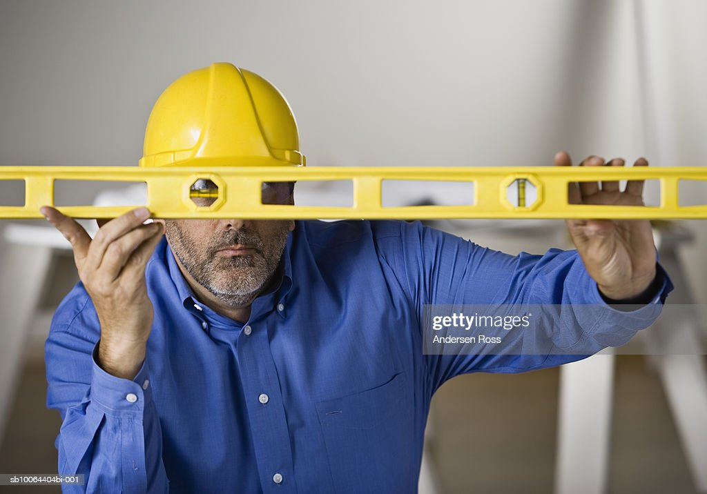 Construction worker holding level over face : Stock Photo