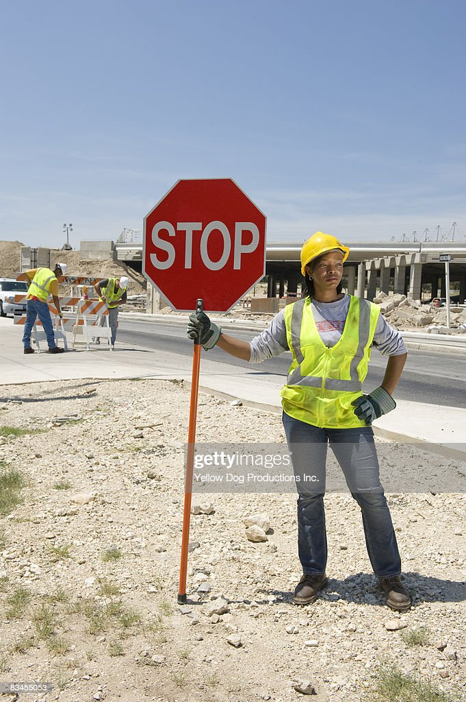 Construction worker holding stop sign for traffic