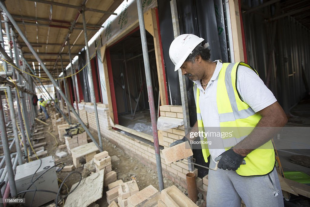 A construction worker holds a brick as he works at the Oval Quarter, a shared ownership, private and social residential housing complex developed by Higgins Group Plc in partnership with Nottinghill Housing and Pinnacle Regeneration Group, in London, U.K., on Monday, Aug. 5, 2013. U.K. house prices rose 0.8 percent in July, from 0.3 percent the previous month, Nationwide Building Society said. Photographer: Simon Dawson/Bloomberg via Getty Images