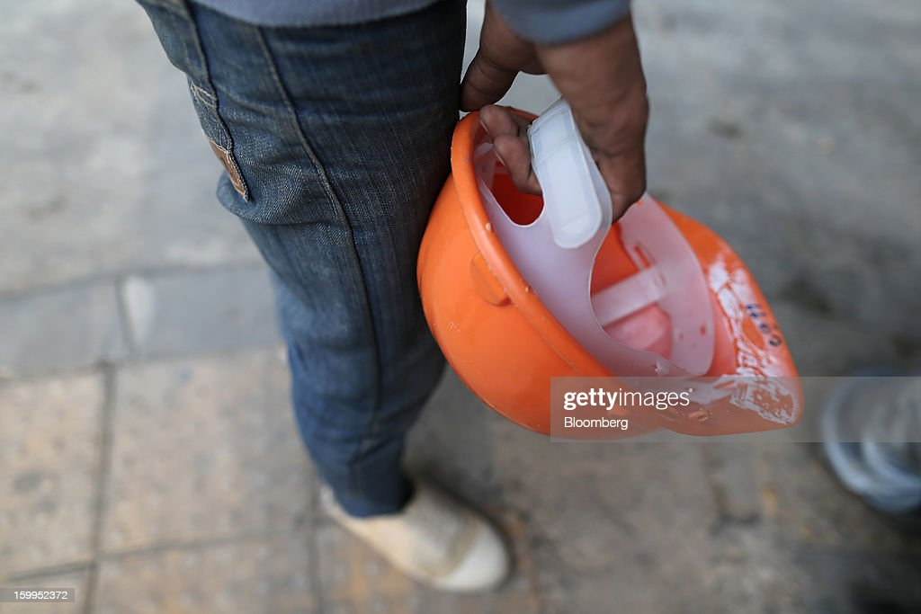 A construction worker holds a safety hat as he stands outside a building site at Siam Square in Bangkok, Thailand, on Wednesday, Jan. 23, 2013. Prime Minister Yingluck Shinawatra's government last month approved a new round of increases in the daily minimum wage to 300 baht ($9.8) from the beginning of this year, after a similar raise in April in seven provinces including Bangkok. Photographer: Dario Pignatelli/Bloomberg via Getty Images