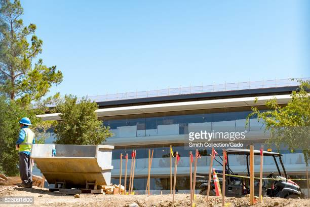 A construction worker in a high visibility vest and blue hard hat stands with construction equipment in front of a portion of the Apple Park known...