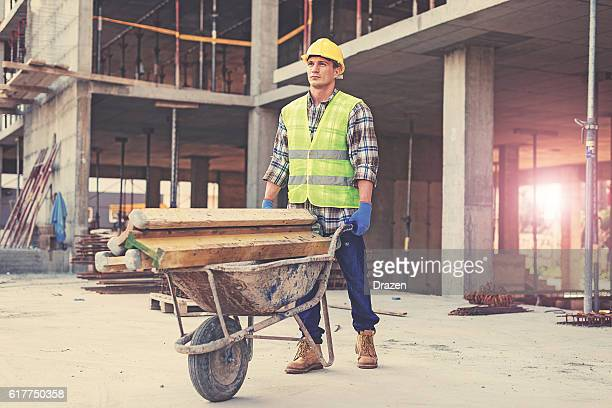 Construction worker in reflective clothing pushing wheelbarrow