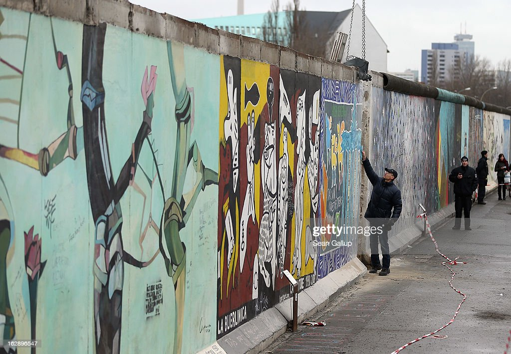 A construction worker inspects a section of the East Side Gallery, which is the longest still-standing portion of the former Berlin Wall, before attempting to remove it with a crane as police stand nearby on March 01, 2013 in Berlin, Germany. A real estate developer is planning to build a 14-storey apartment building between the Wall and the Spree River and needs to remove a 25-meter long Wall section in order to allow access to the construction site. Critics, including East Side Gallery mural artists and Spree River embankment development opponents, decry the move, citing the importance of the East Side Gallery's status as a protected landmark and a major tourist attraction. The East Side Gallery is approximately 1.3 kilometers long.