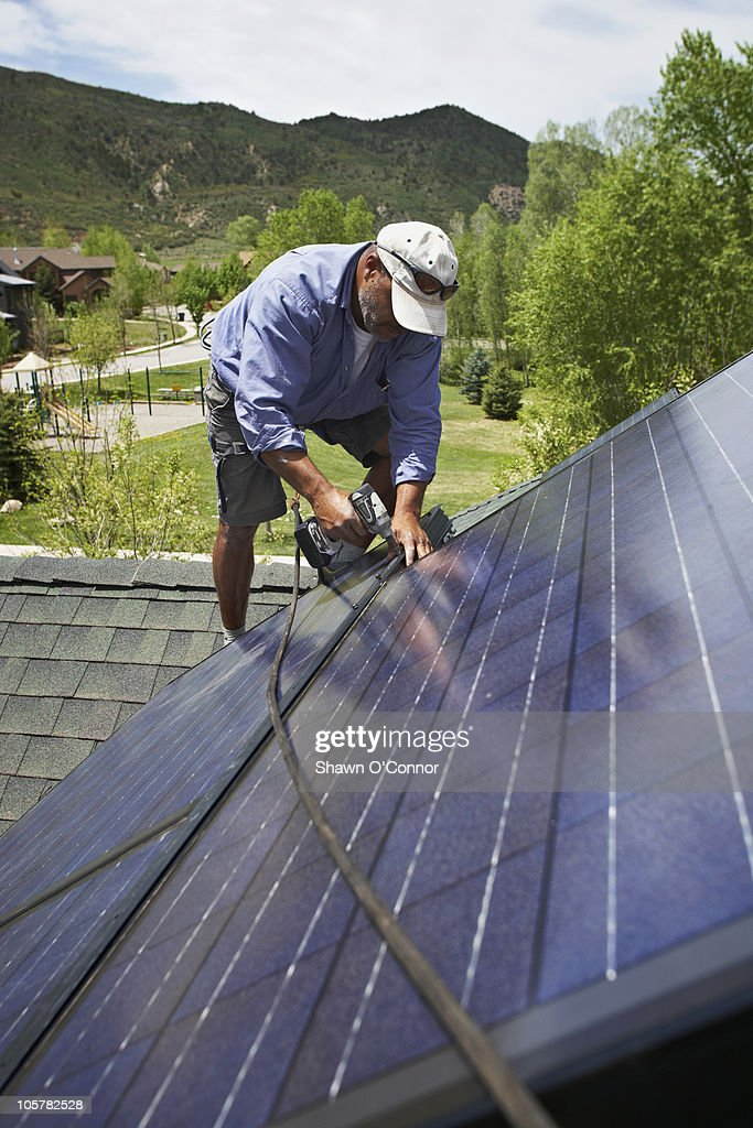 Construction worker installing solar panel on roof : Stock Photo