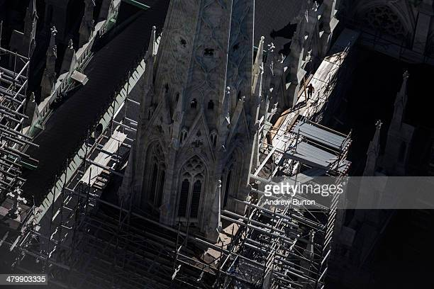 A construction worker is seen working on top of St Patrick's Cathedral from the top of Rockefeller Center on March 21 2014 in New York City After a...