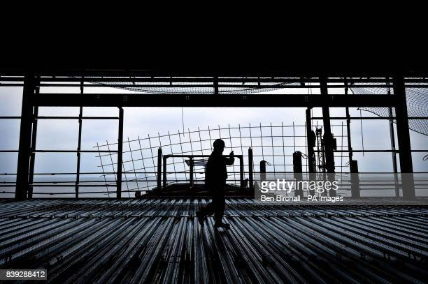 A construction worker is silhouetted as he carries steel mesh past the end of the pier on the second level as construction continues on the Grand...