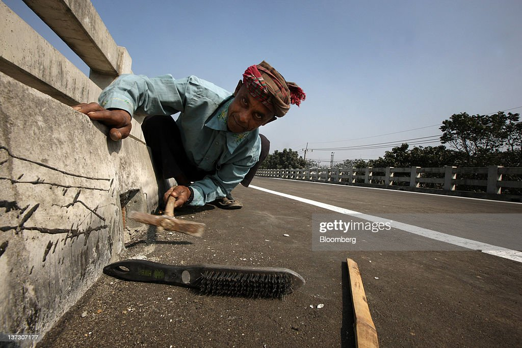 A construction worker labors on an overpass in Chittagong, Bangladesh, on Saturday, Jan. 14, 2011. Bangladesh's central bank this month raised interest rates for the second time in four months to curb inflation that has exceeded 9 percent since the start of 2011. Photographer: Tomohiro Ohsumi/Bloomberg via Getty Images