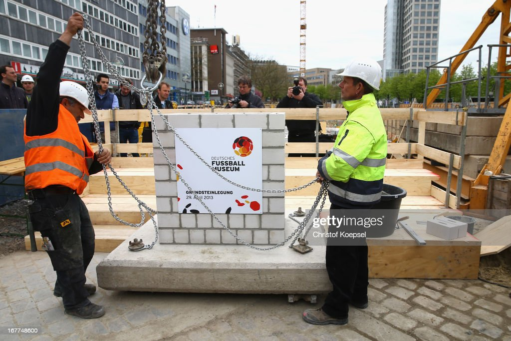 Construction worker lift up a part of masonry on a crane at the construction area during the DFB Football Museum groundbreaking ceremony at Koenigswall on April 29, 2013 in Dortmund, Germany.