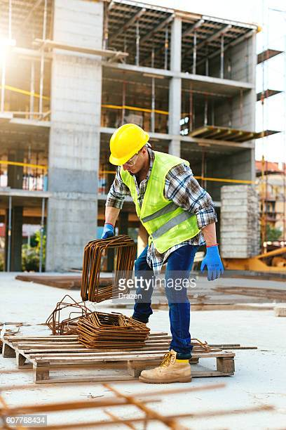 Construction worker lifting armature on construction site