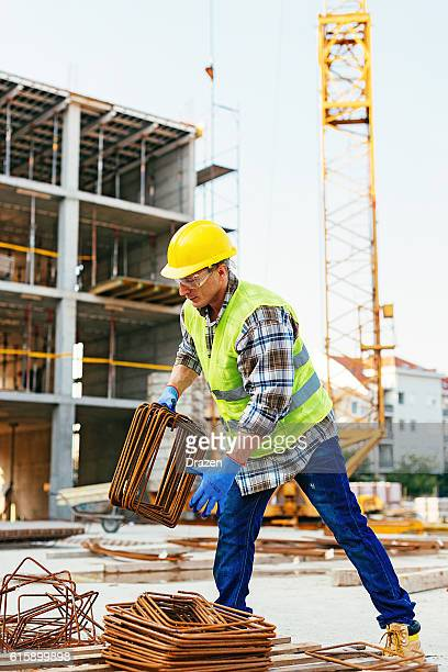Construction worker lifting steel rods