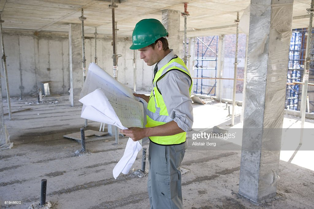 Construction worker looking at plans on building site : Stock Photo