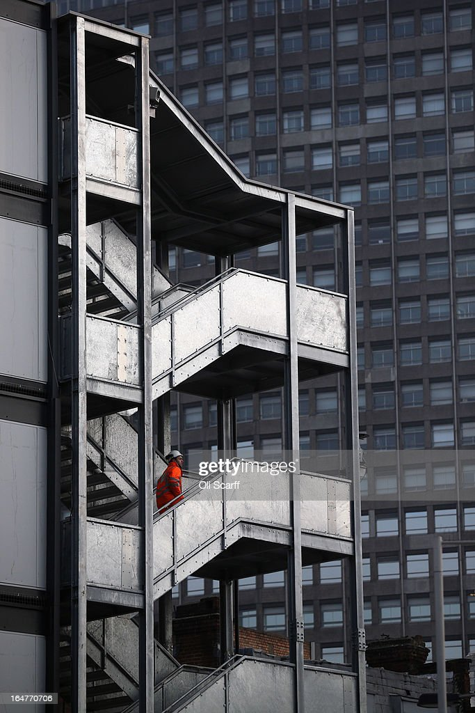 A construction worker looks out from a building site opposite Victoria train station on March 27, 2013 in London, England.