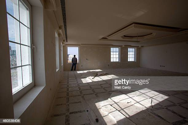 A construction worker looks out of a window in a bedroom in the replica White House a $20million villa being built inside Dream City a new exclusive...