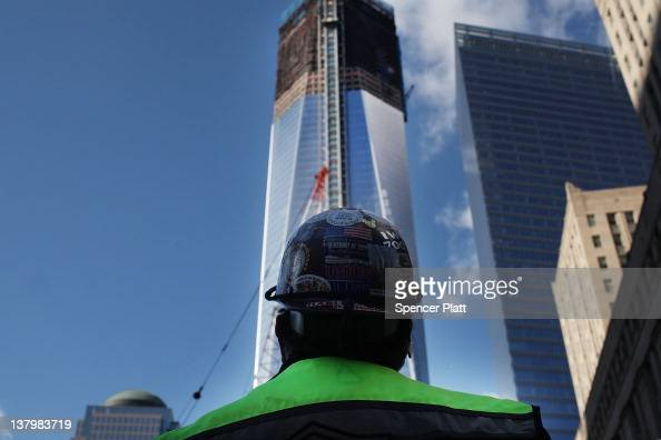 A construction worker looks up at One World Trade Center the central skyscraper under construction at Ground Zero on January 30 2012 in New York City...