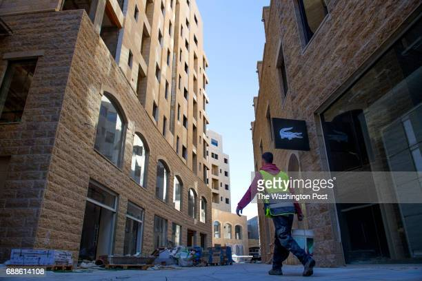 A construction worker makes cement near the LaCoste retail shop and apartments at Rawabi a highend multiuse development in Rawabi West Bank on April...