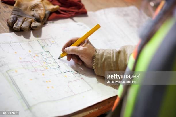 Construction worker marking blueprints