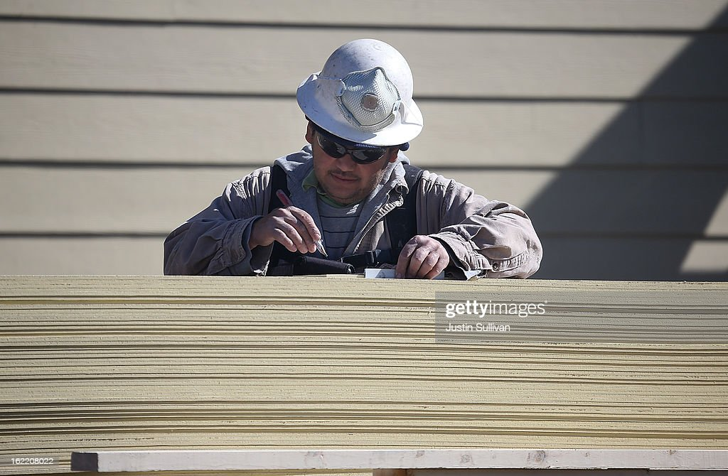 A construction worker measures wood siding at the Arbor Rose housing development on February 20, 2013 in San Mateo, California. The Commerce Department reported that new housing starts dropped 8.5% in January following a 15.7% increase one month earlier.