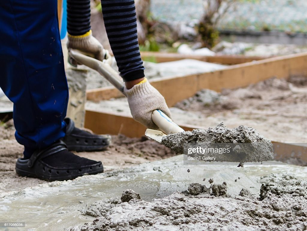 Construction worker mixing cement : Stock Photo
