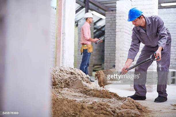 Construction worker mixing concrete with shovel