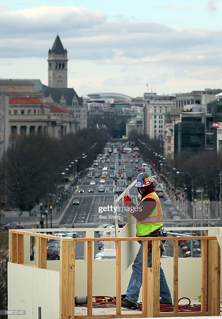 A construction worker moves a piece board as he works on the Inaugural platform December 11, 2012 on Capitol Hill in Washington, DC. President Barack Obama will be sworn in for his second term as the President of the United States during a private ceremony on January 20 and a public ceremony on January 21, 2013.