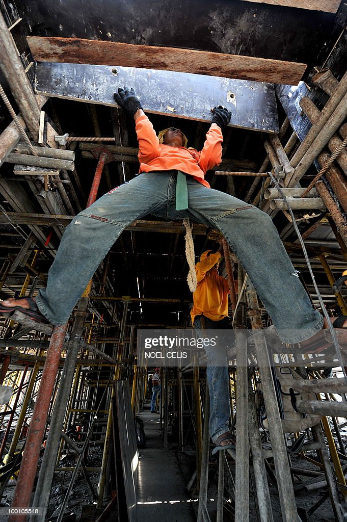 A construction worker nails a plywood on the ceiling of an unfinished building in Manila on May 21, 2010. President-elect Benigno Aquino has an economics degree but he will need a lot more than that to solve the problems that have turned workers into the Philippines' most famous export.