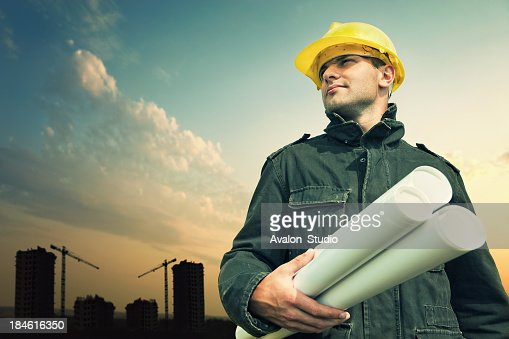Construction worker on a construction site with blue prints.
