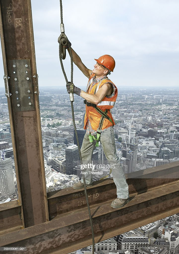 Construction worker on beam above cityscape (digital composite) : Stock Photo