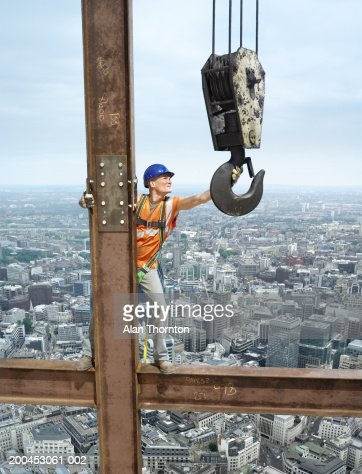 Construction worker on beam above cityscape (digital composite)