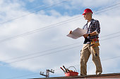 Engineer standing on rooftop looking away and holding blueprint project. Mature construction worker kit standing on rooftop with copy space. Workman inspecting construction site with sheet of paper in