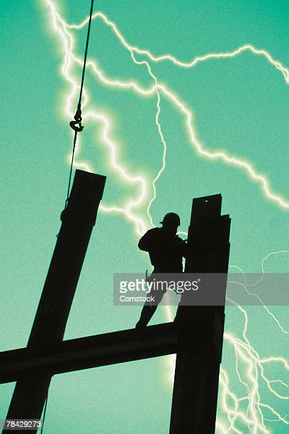Construction worker on steel beams with lightning bolt