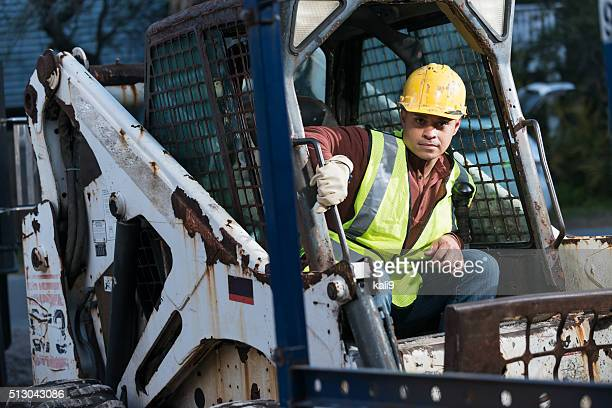 Construction worker operating a back hoe