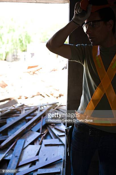 Construction worker pausing work, hand on forehead